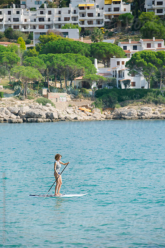 Woman doing Stand Up paddle Surf by Blai Baules for Stocksy United