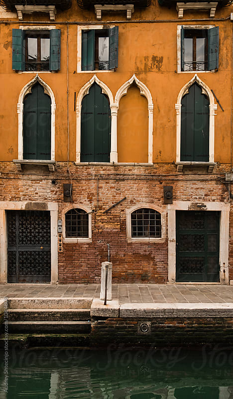 Building with yellow rustic facade with water canal in front of it. Venice/Italy by Audrey Shtecinjo for Stocksy United
