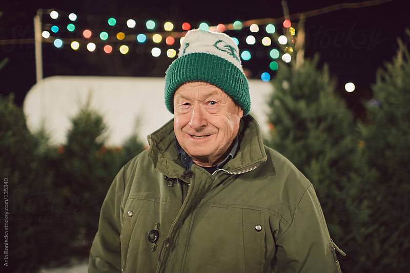 A portrait of an old man in a christmas tree lot by Ania Boniecka for Stocksy United