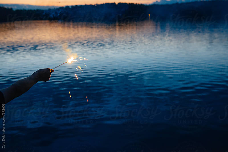 Child's arm with sparkler over lake water by Cara Dolan for Stocksy United