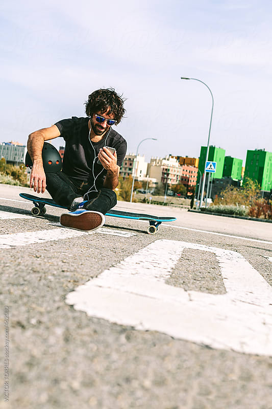 Young Man Sitting on a Longboard and Using a Mobile Phone by VICTOR TORRES for Stocksy United