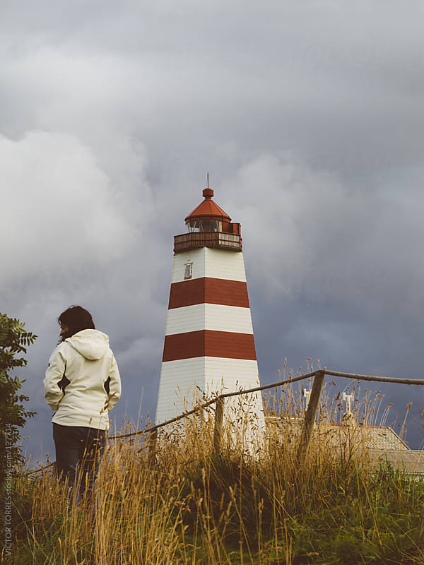 Woman besides Alnes Lighthouse by VICTOR TORRES for Stocksy United