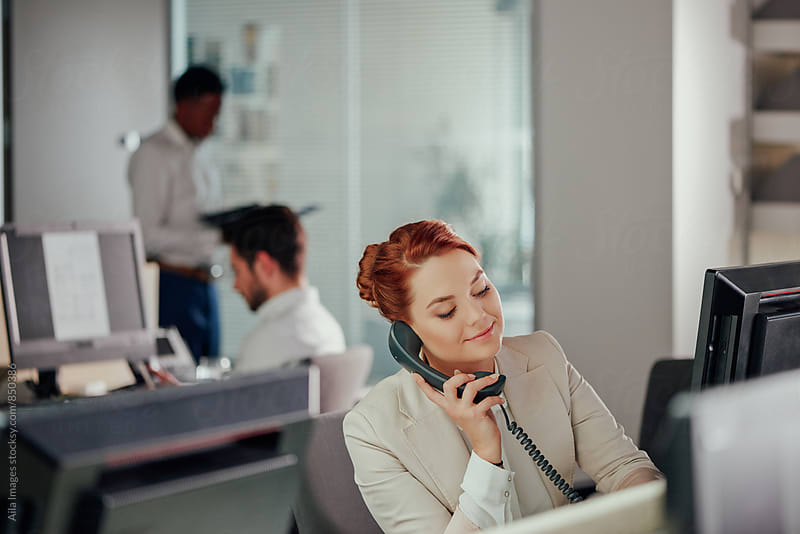 Business woman working at desk in busy modern office by Aila Images for Stocksy United