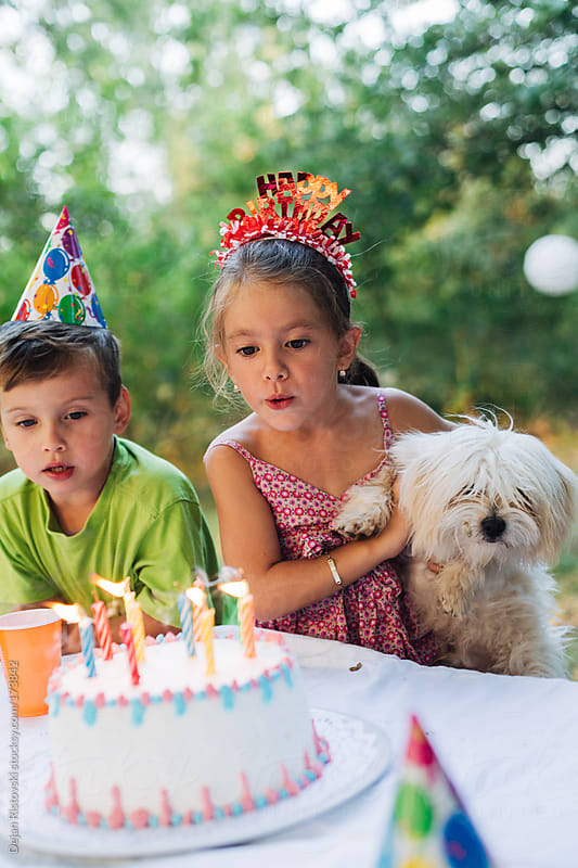 Girl blowing candles on a outdoor Birthday party by Dejan Ristovski for Stocksy United