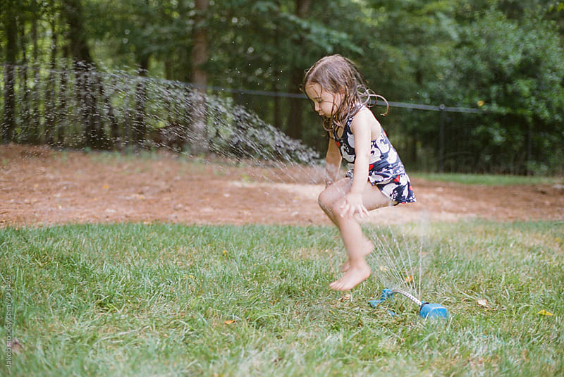 Young girl playing with a sprinkler in her backyard by Jakob for Stocksy United