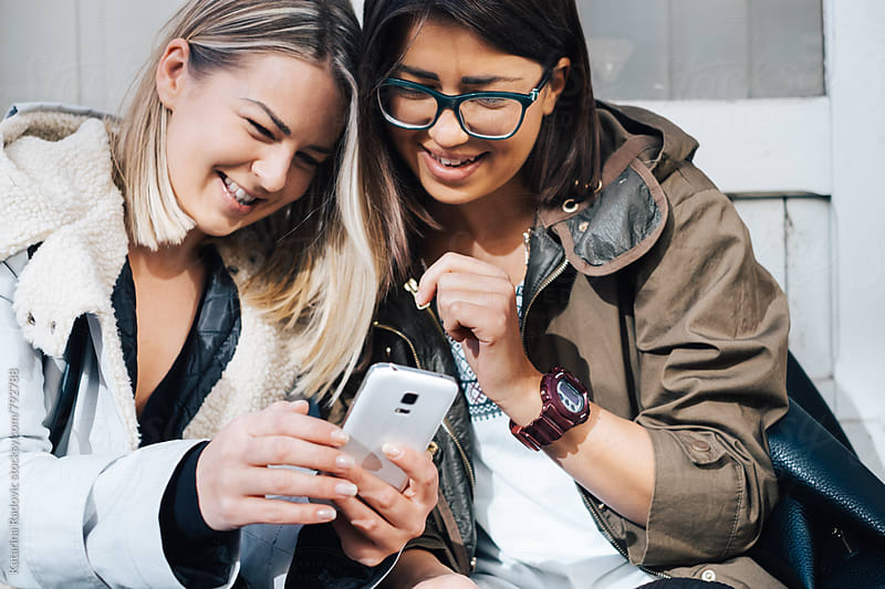 Two Female Friends Using Phone and Smiling by Katarina Radovic for Stocksy United