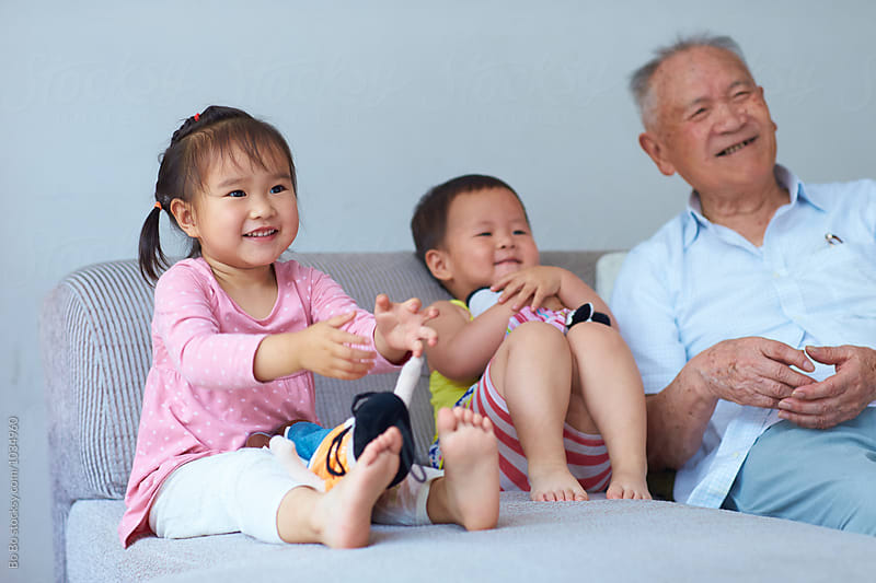 happy senior asian man having fun with his two great granddaughter indoor by Bo Bo for Stocksy United