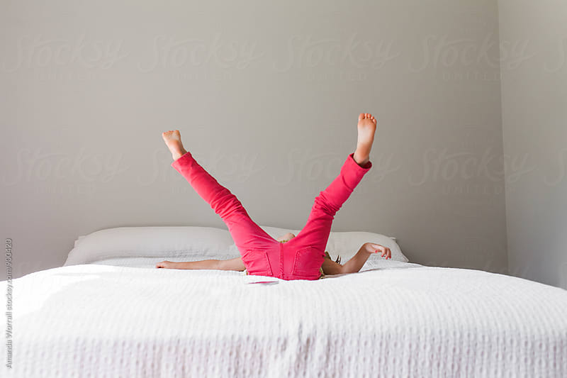 Unrecognizable young girl wearing bright pink pants falls on her back while jumping on bed by Amanda Worrall for Stocksy United