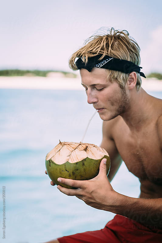 Young man drinking fresh coconut with a straw on a boat at sea. by Soren Egeberg for Stocksy United