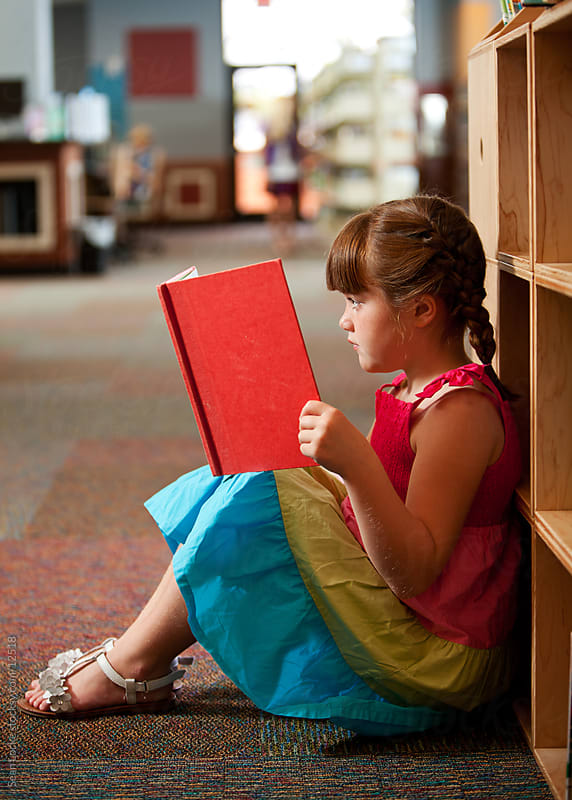 Library: Young Girl Concentrating on Reading by Sean Locke for Stocksy United