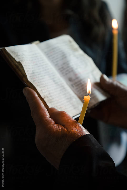 Priest reading the bible and holding a candle by Pixel Stories for Stocksy United