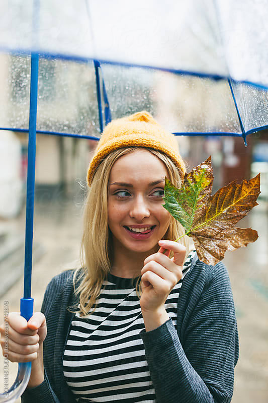 Woman showing a leaf standing on the street in a rainy day. by BONNINSTUDIO for Stocksy United