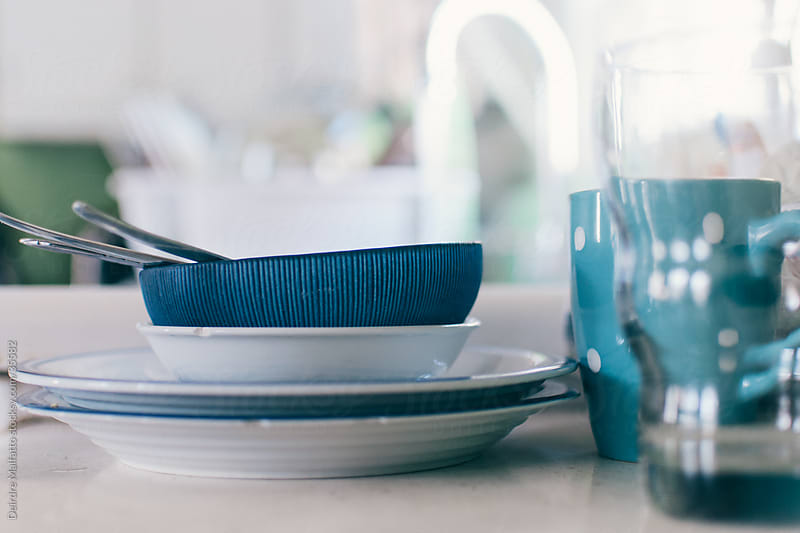 dirty dishes stacked on a counter next to a sink by Deirdre Malfatto for Stocksy United