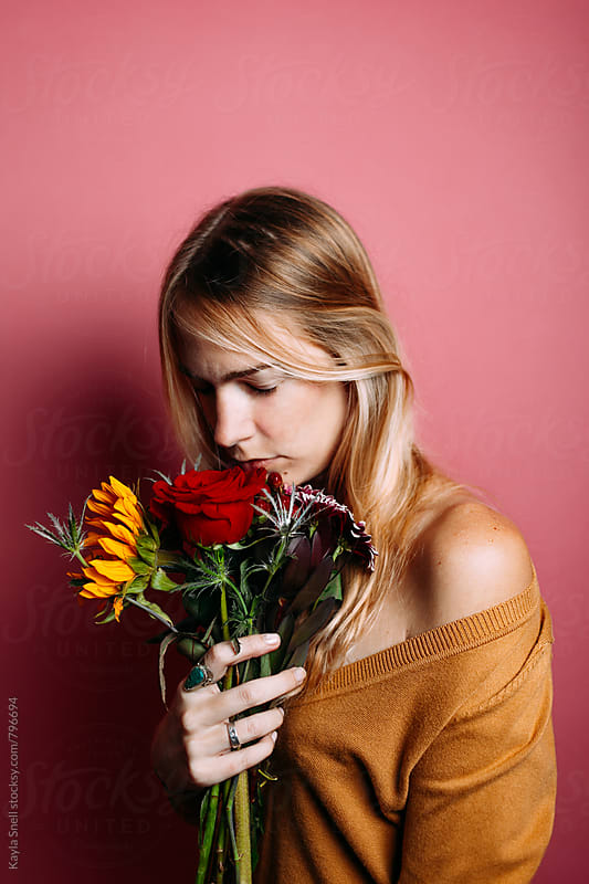 Woman smelling flowers by Kayla Snell for Stocksy United