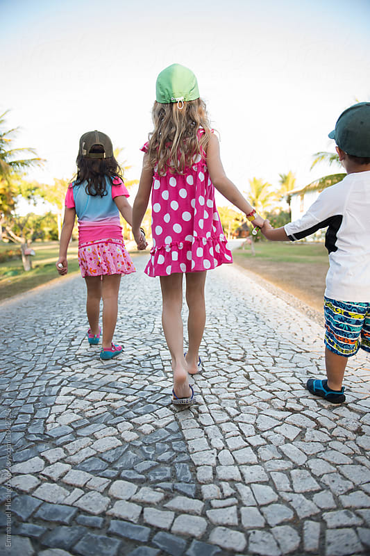 Three small kids holding hands and walking down a paved walkway at a resort in Bahia, Brazil by Emmanuel Hidalgo for Stocksy United