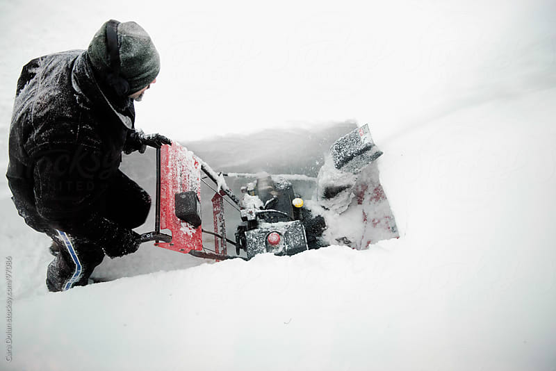 Man pushes a snow blower through very deep snow during a winter storm by Cara Dolan for Stocksy United