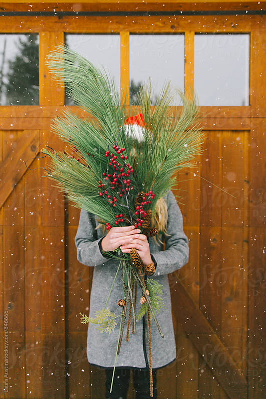 Woman Holding Christmas Branches In Front Of Face In Snow by Laura Austin for Stocksy United