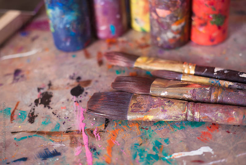 Paint brushes and bottles of paint in an artist's studio by Carolyn Lagattuta for Stocksy United