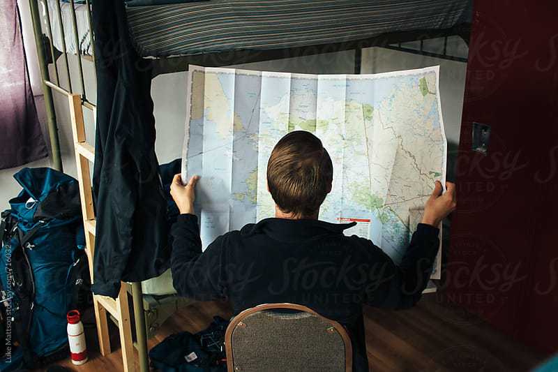 Young Man Looking At Map by Luke Mattson for Stocksy United