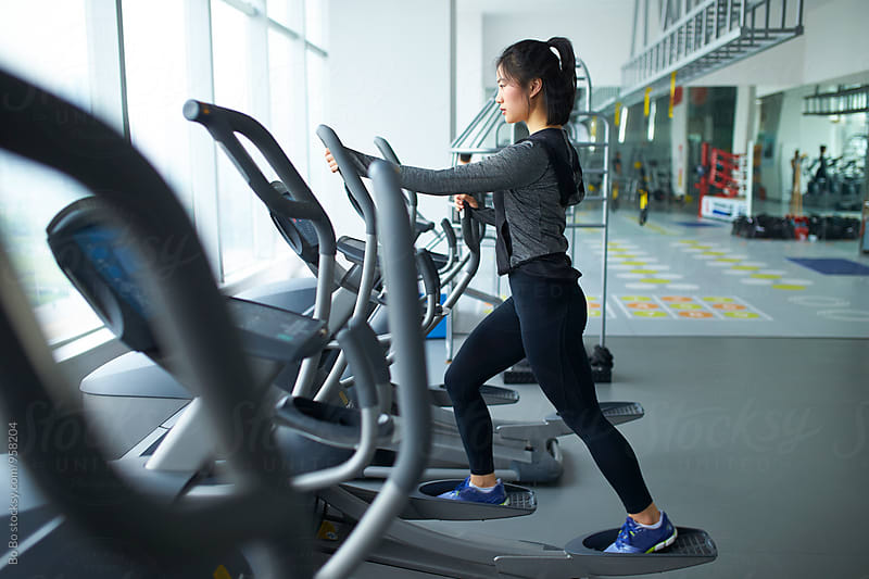 young asian woman running in gym by Bo Bo for Stocksy United