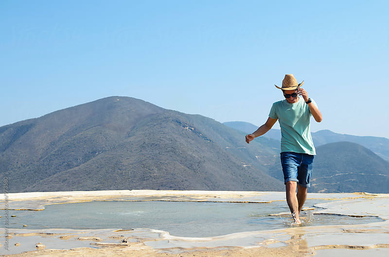 Happy young guy walking in a natural pool at the edge of Petrifi by Alice Nerr for Stocksy United