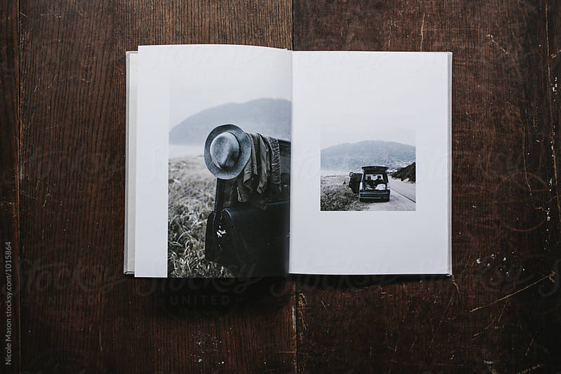 open book with photos of traveler's car at coast by Nicole Mason for Stocksy United