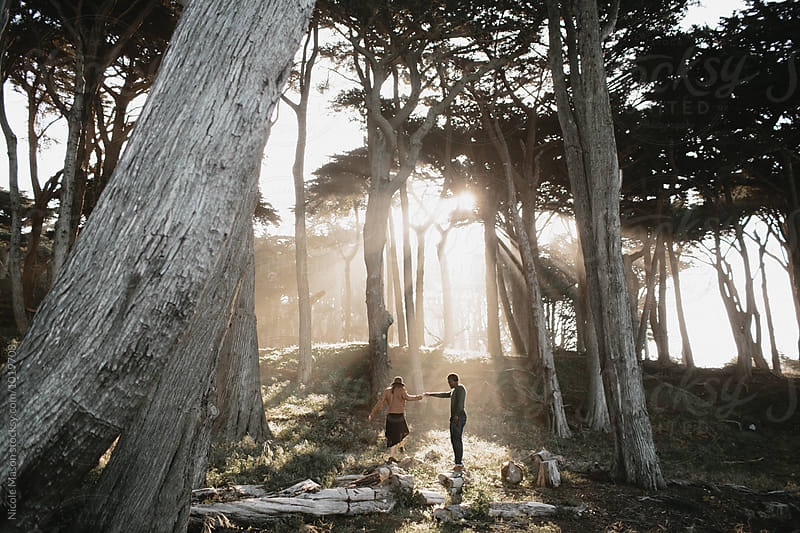 couple walking through trees with rays of sun by Nicole Mason for Stocksy United
