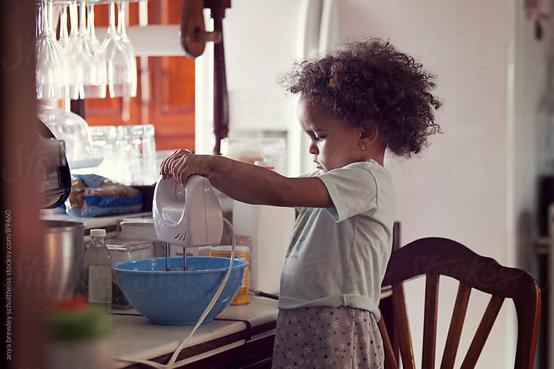 Portrait of young girl baking in the kitchen by anya brewley schultheiss for Stocksy United