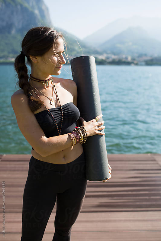Brunette woman holding a yoga mat by michela ravasio for Stocksy United