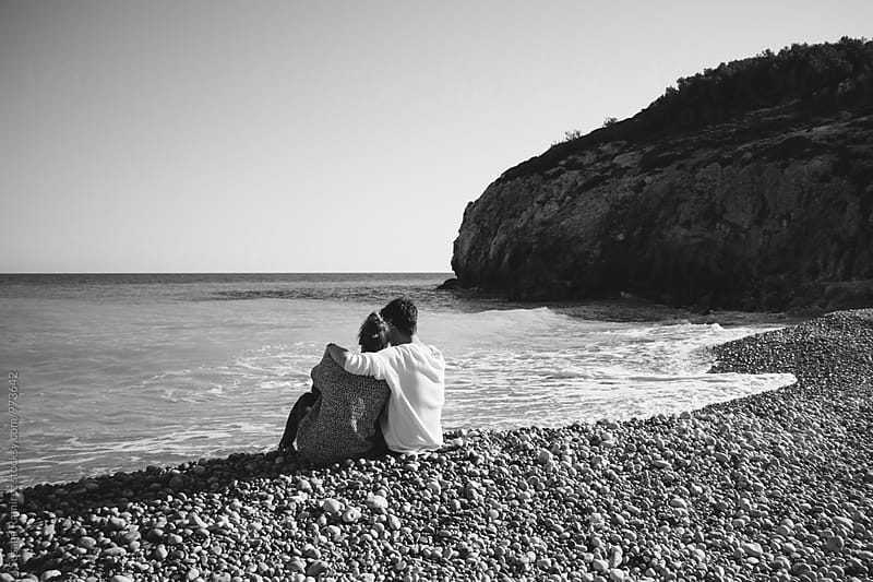 Couple embracing on the beach by Susana Ramírez for Stocksy United