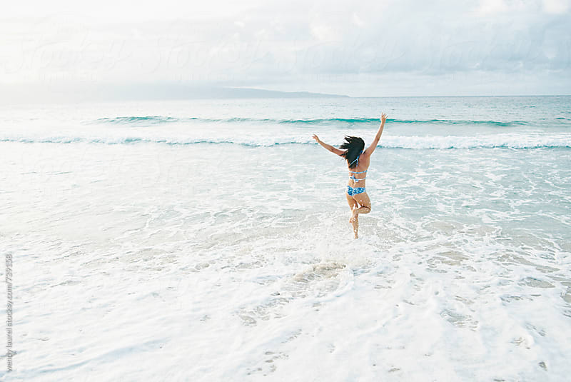 young woman running into ocean with joy  by wendy laurel for Stocksy United