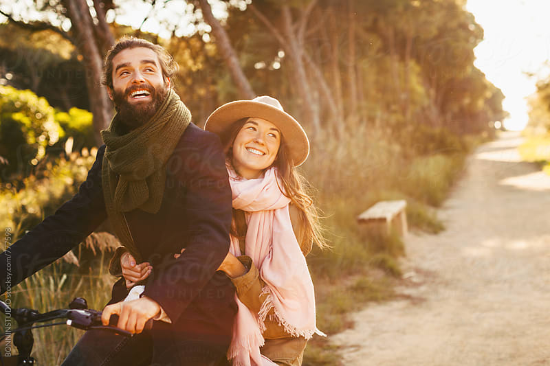 Young hipster couple riding a bicycle in the forest. by BONNINSTUDIO for Stocksy United