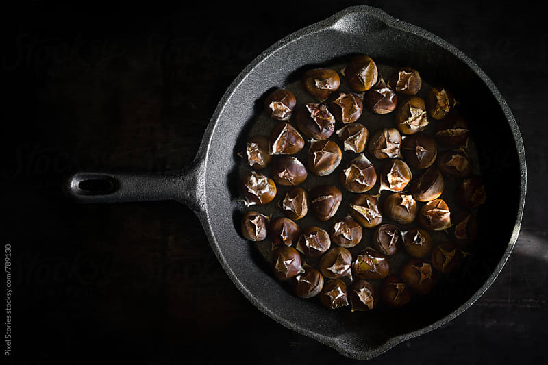 Roasted chestnuts in a cast iron pan by Pixel Stories for Stocksy United