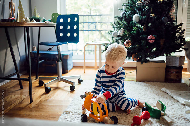 Cute Boy Playing With Wooden Toys at Christmastime by Lumina for Stocksy United