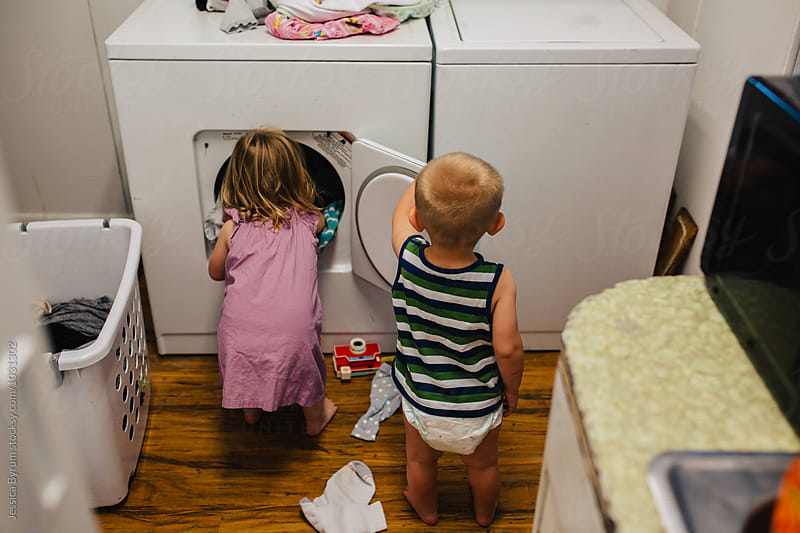 Toddler siblings helping to unload the dryer. by Jessica Byrum for Stocksy United