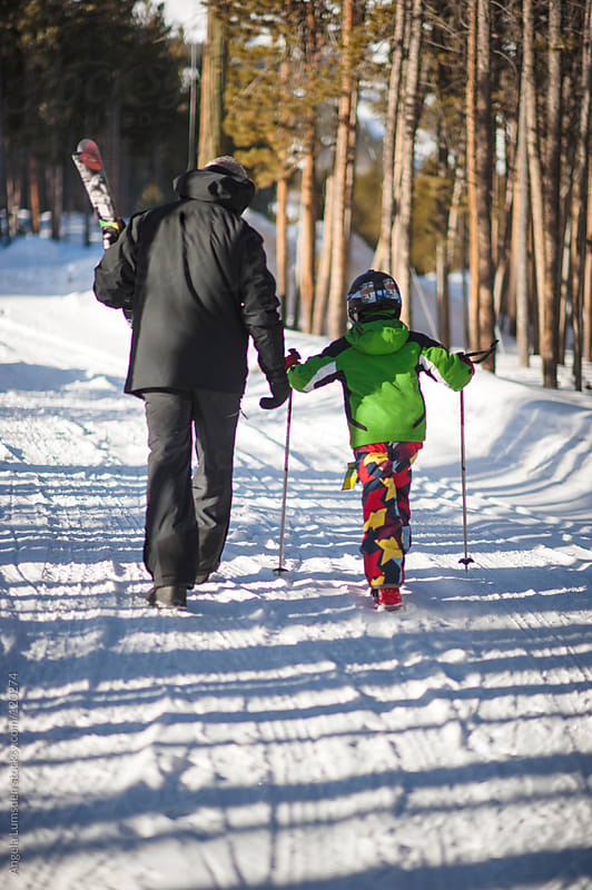 Boy and his father set off for a day skiing by Angela Lumsden for Stocksy United