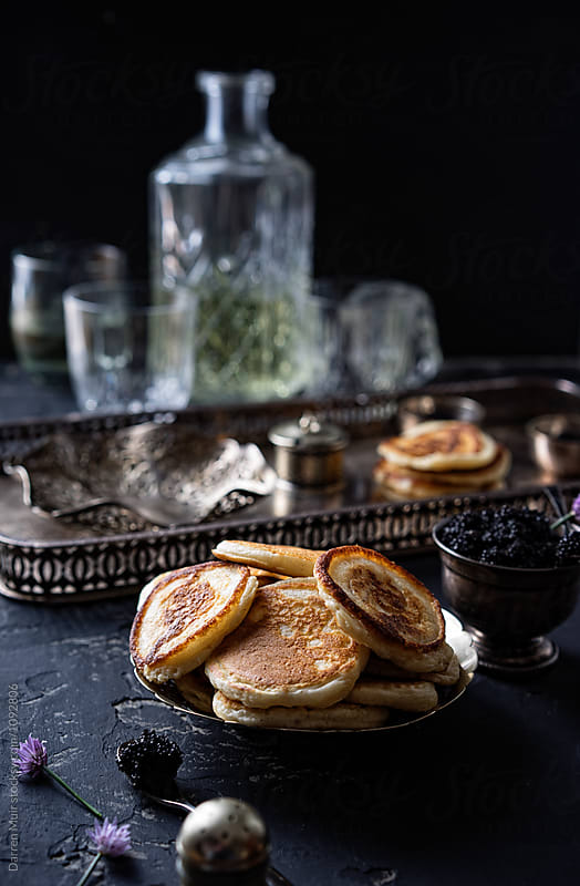 Blinis and ingredients for preparing them on a table,with drinks in the background. by Darren Muir for Stocksy United