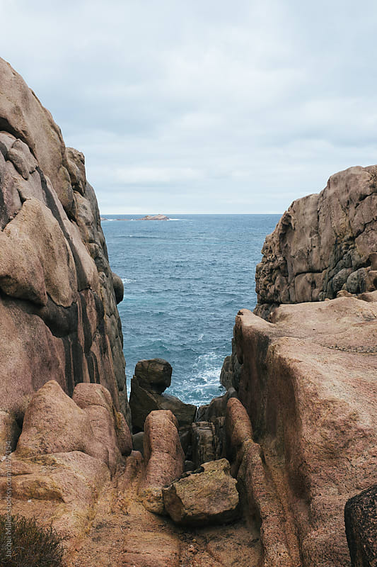View of the Indian Ocean through a gap in an outcrop of rock by Jacqui Miller for Stocksy United