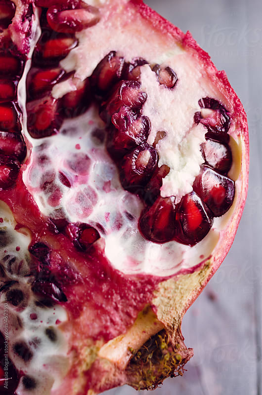 Close up view of half pomegranate fruit by Alessio Bogani for Stocksy United