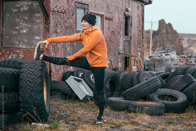 Active woman stretching outdoors after running by Søren Egeberg Photography for Stocksy United