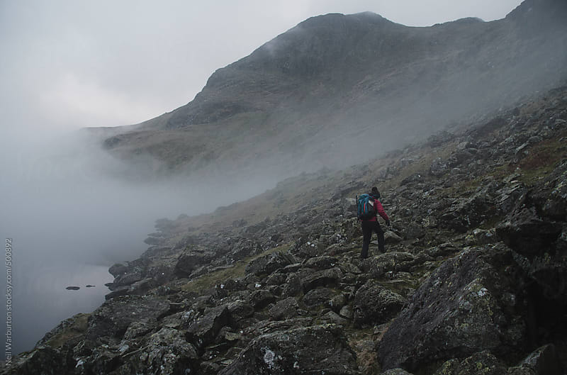Hiker in misty landscape by Neil Warburton for Stocksy United