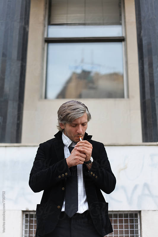Businessman smoking cigarette in front of a buidling  by Marija Mandic for Stocksy United