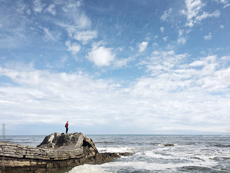 A man standing on rocks looking out to sea by James Ross for Stocksy United