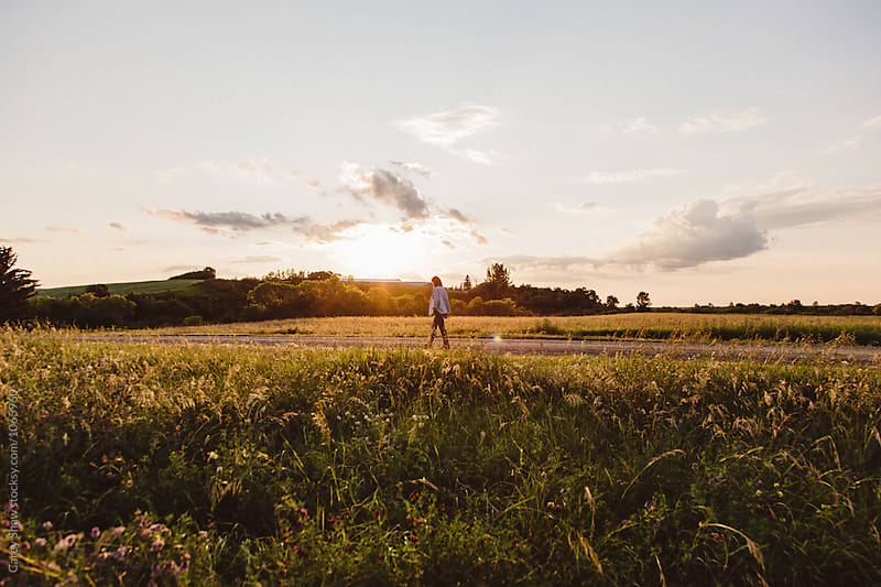 Woman walking on countryside road at dusk by Carey Shaw for Stocksy United