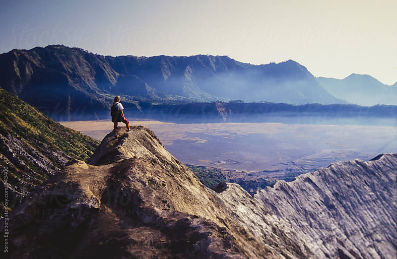 Girl standing on the rim of an active volcano looking at the landscape by Soren Egeberg for Stocksy United