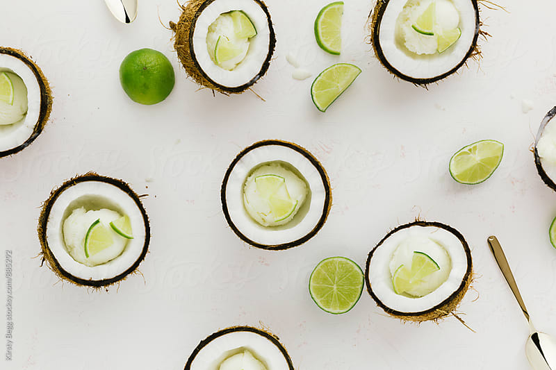 Flat lay of coconut shells filled with ice cream and lime by Kirsty Begg for Stocksy United