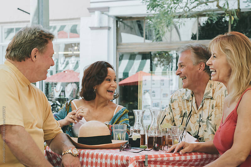 Youthful Senior Retirees Chatting over Drinks at Outdoor Cafe on Summer Holiday Vacation in Miami by Joselito Briones for Stocksy United