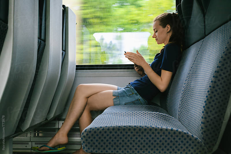 Young woman using tablet traveling by train by Ilya for Stocksy United