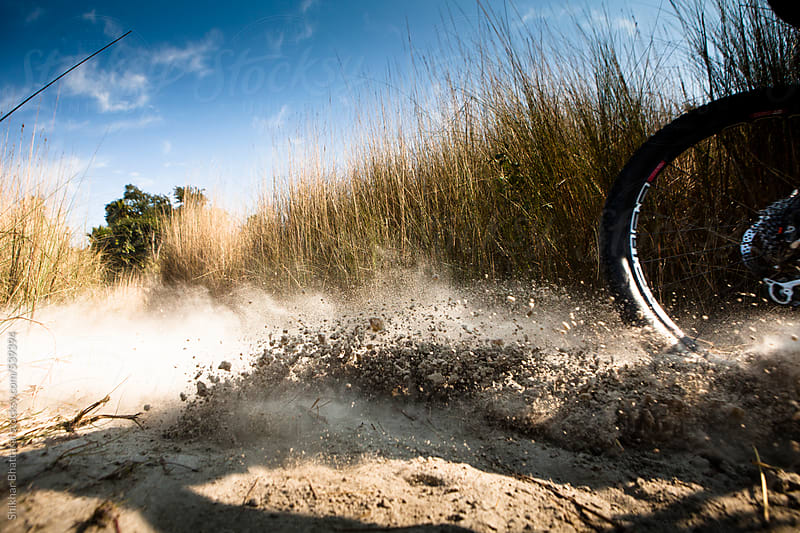Dirt flying by as a mountain biker makes a turn on the turf. by Shikhar Bhattarai for Stocksy United