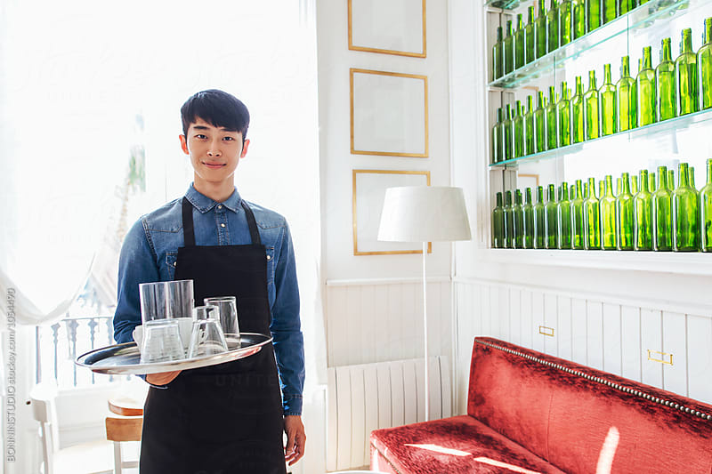 Handsome asian male entrepreneur working in a cool restaurant. by BONNINSTUDIO for Stocksy United